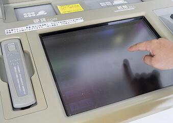 ATMを操作する男性の手